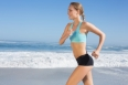 Fit woman jogging on the beach on a sunny day